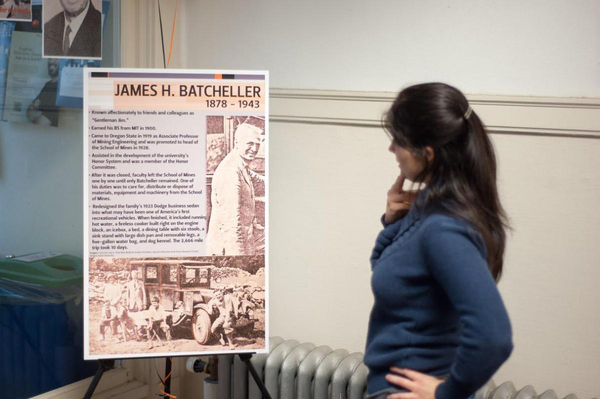 student looking at poster of Batcheller Hall