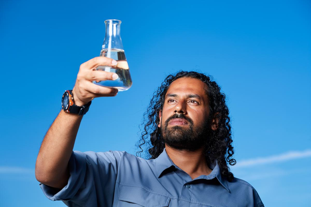 Bahman Abbasi holds a beaker of fresh water.