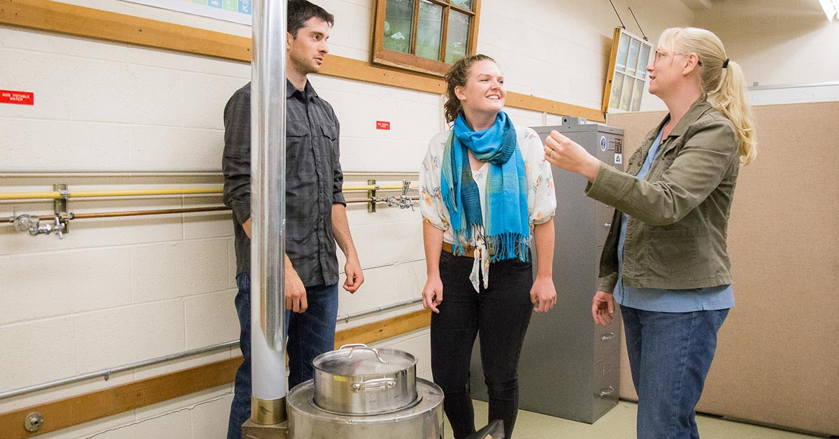 Nick Moses and Grace Burleson, both dual Master's students in mechanical engineering and anthropology, and Nordica MacCarty, assistant professor of mechanical engineering, demonstrate the InStove, a highly-efficient, clean-burning cook stove designed for use in low-resource environments.