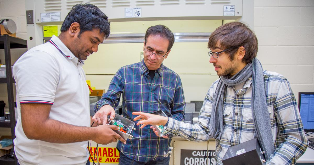Harish Gadey, Abi Farsoni, and Steven Czyz show off their radioxenon detector.
