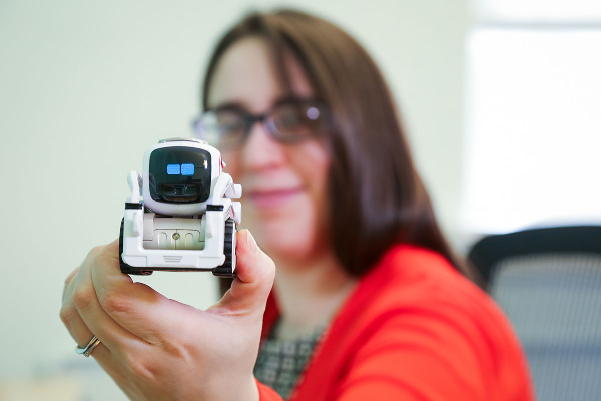 Naomi Fitter, assistant professor of robotics, holds Cozmo, a workplace assistant robot programmed to encourage people to take breaks throughout their work day.