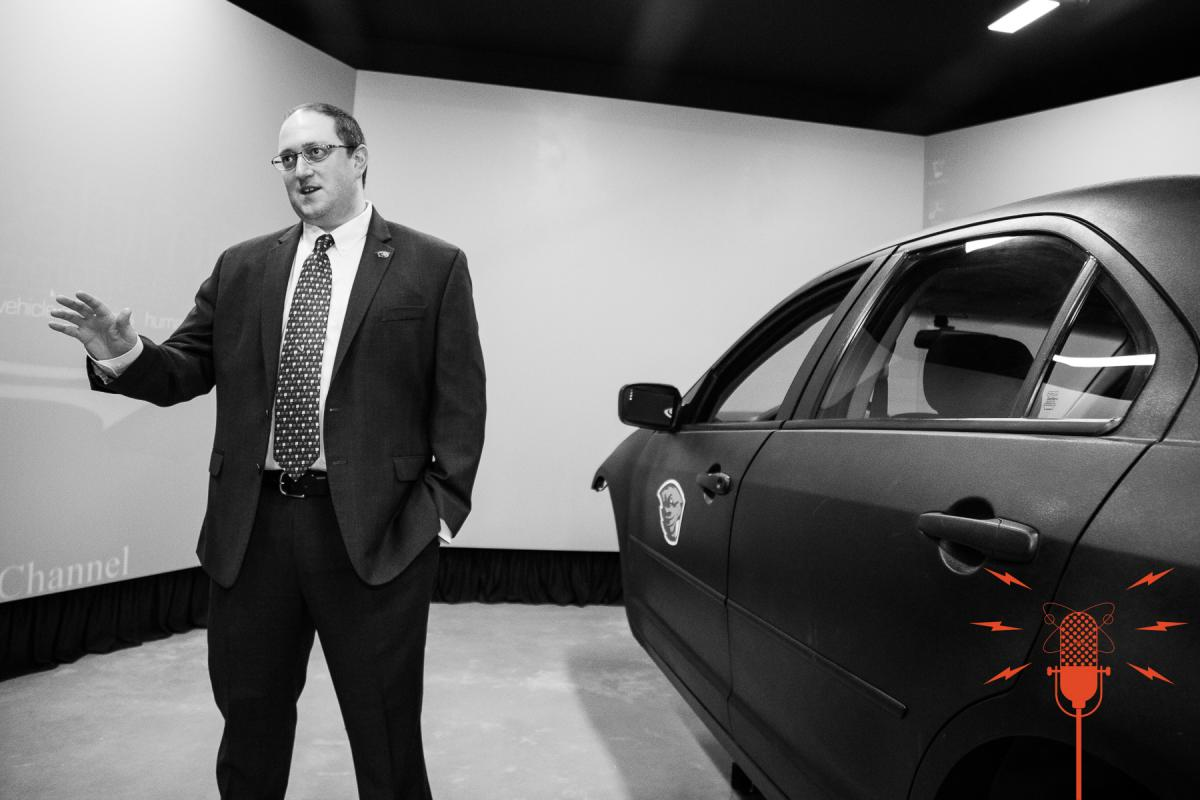 Associate Professor David Hurwitz stands near the driving simulator at Oregon State University