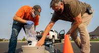 2 men stand over manhole cover with testing kits for COVID-19